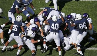 FILE - In this Sept. 27, 2014, file photo, Northwestern quarterback Trevor Siemian scores on a quarterback sneak during the first quarter of an NCAA college football game against Penn State in State College, Pa. It has become common for teams to line up in shotgun formation on short-yardage plays, forgoing the possibility of a quarterback sneak for the ability to use the entire playbook. (AP Photo/Gene J. Puskar, File)