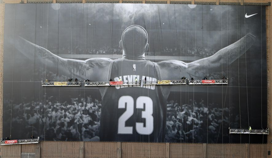 Workmen finish hanging a 10-story-tall Nike banner with LeBron James likeness on a building in Cleveland Thursday, Oct. 30, 2014. (AP Photo/Mark Duncan)