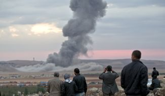 People watch smoke from an airstrike by the US-led coalition rising outside Kobani, Syria, from a hilltop on the outskirts of Suruc, at the Turkey-Syria border, Thursday, Oct. 23, 2014. Kobani, also known as Ayn Arab, and its surrounding areas, has been under assault by extremists of the Islamic State group since mid-September and is being defended by Kurdish fighters. (AP Photo/Vadim Ghirda)
