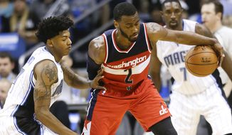 Washington Wizards' John Wall (2) makes a move to get around Orlando Magic's Elfrid Payton, left, during the second half of an NBA basketball game in Orlando, Fla., Thursday, Oct. 30, 2014.  Washington won 105-98. (AP Photo/John Raoux)
