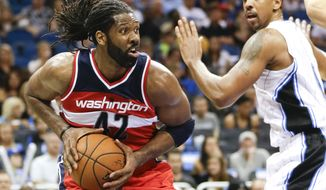 Washington Wizards' Nene (42) looks to pass the ball as he gets around Orlando Magic's Channing Frye during the first half of an NBA basketball game in Orlando, Fla., Thursday, Oct. 30, 2014. (AP Photo/John Raoux)
