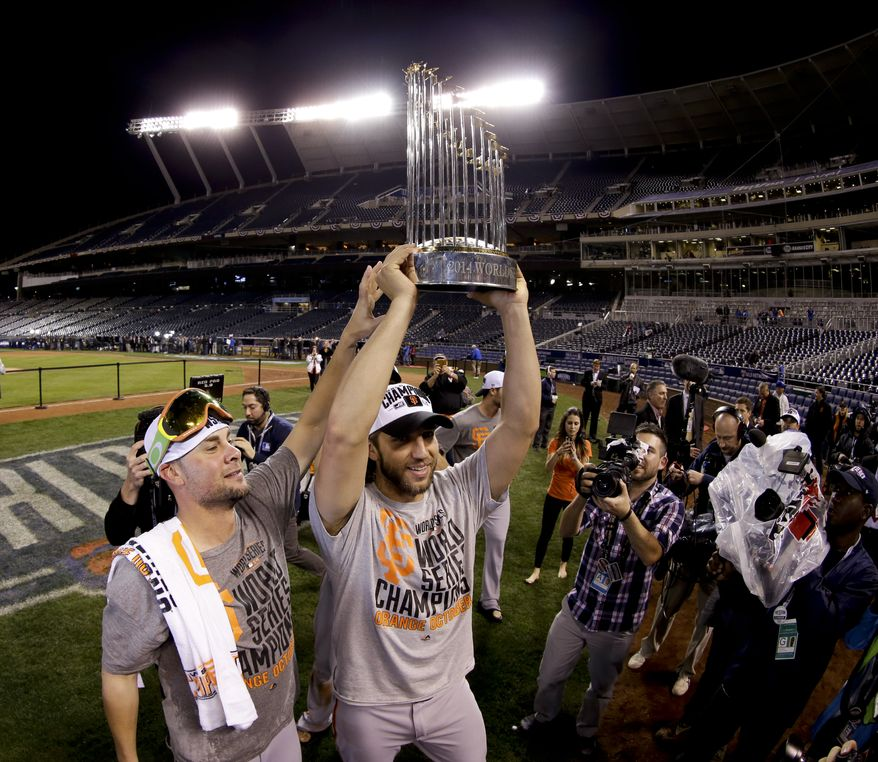 San Francisco Giants pitcher Madison Bumgarner holds up the trophy after their win in Game 7 of baseball's World Series against the Kansas City Royals Wednesday, Oct. 29, 2014, in Kansas City, Mo. (AP Photo/Charlie Riedel)