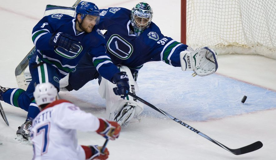 Montreal Canadiens' Max Pacioretty, lower left, scores the tying goal against Vancouver Canucks' goalie Ryan Miller as Yannick Weber, of Switzerland, stretches in vain to stop the puck during the third period of an NHL hockey game, Thursday, Oct. 30, 2014 in Vancouver, British Columbia. (AP Photo/The Canadian Press,  Darryl Dyck)