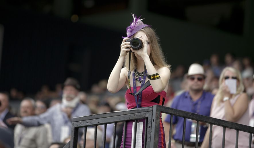 A fan takes a picture at Santa Anita Park before the Breeders Cup horse races Friday, Oct. 31, 2014, in Arcadia, Calif. (AP Photo/Jae C. Hong)