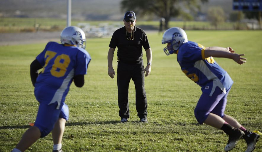 In this Oct. 22, 2014 photo, Pahranagat Valley Panthers head coach Ken Higbee directs his team during practice in Alamo, Nev. To call Alamo a one stoplight town would be to elevate the status of the small collection of buildings surrounding the high school some 90 miles north of Las Vegas. (AP Photo/John Locher)