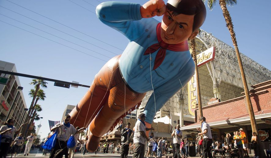 People march with the inflatable cowboy during Nevada Day Parade in Las Vegas, Friday, Oct. 31, 2014. Nevada is marking its 150th anniversary of statehood with ceremonies and parades, including a daytime procession in Las Vegas marking the state holiday and another, nine hours later, featuring costumed Halloween revelers. (AP Photo/Las Vegas Review-Journal, Jeff Scheid) LOCAL TELEVISION OUT; LOCAL INTERNET OUT; LAS VEGAS SUN OUT
