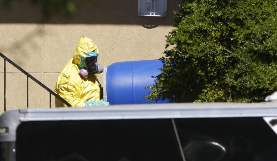 FILE - In this Friday, Oct. 3, 2014, file photo, a hazardous material cleaner removes a blue barrel from the apartment in Dallas, where Thomas Eric Duncan, the Ebola patient who traveled from Liberia to Dallas stayed. The apartment contents were incinerated but nearly a month later, the ashes sit in limbo at a facility in Port Arthur, Texas, as Louisiana officials fight to keep it out of a landfill there.  (AP Photo/LM Otero, File)