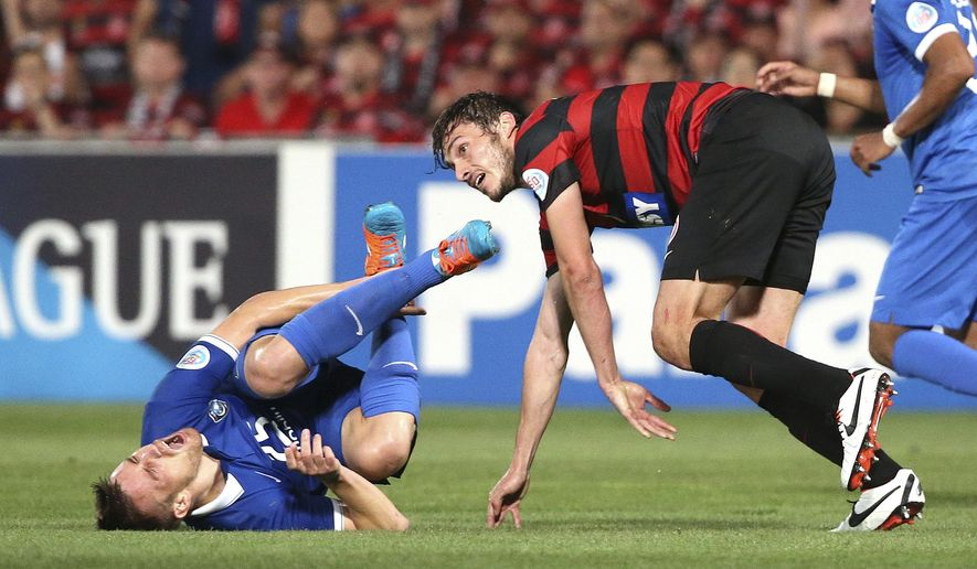 Saudi Arabia's Al Hilal's Mihai Doru Pintilii rolls on the ground after he clashed with Western Sydney Wanderers' Mateo Poljak during their Asian Champions League Final in Sydney, Australia, Saturday, Oct. 25, 2014. (AP Photo/Rob Griffith)