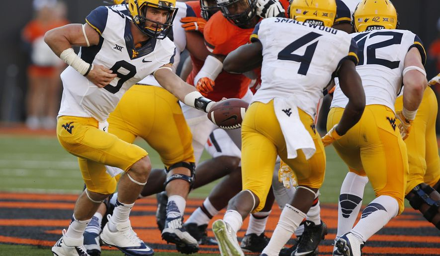 West Virginia quarterback Clint Trickett (9) hands off to teammate Wendell Smallwood (4) in the fourth quarter of an NCAA college football game against Oklahoma State in Stillwater, Okla., Saturday, Oct. 25, 2014. West Virginia won 34-10.(AP Photo/Sue Ogrocki)