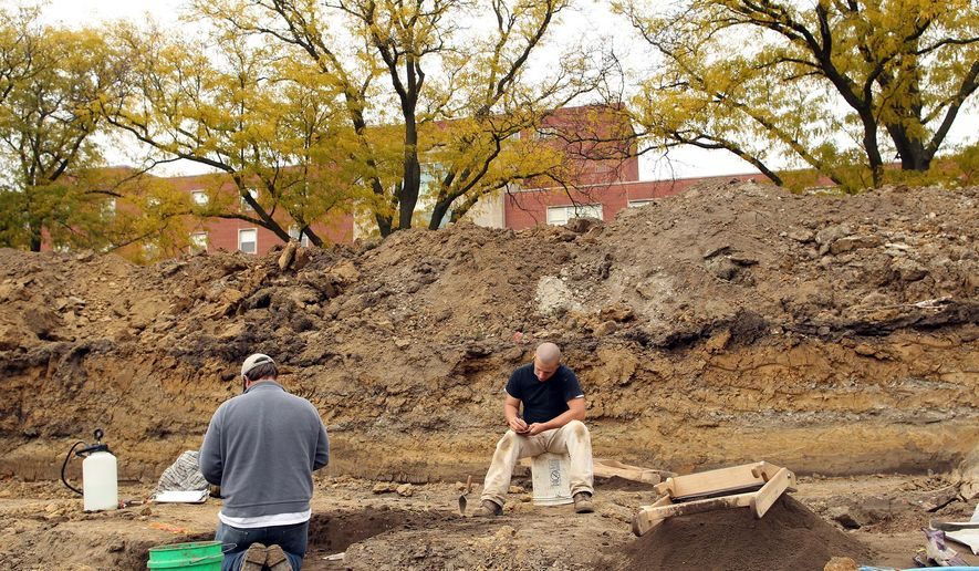 In this Oct. 24, 2014 photo, Dan Horgen, left, and Anson Kritsch, of the Office of the State Archaeologist, work at the excavation site at Hubbard Park in Iowa City, Iowa. After workers discovered antique artifacts earlier this year in the park, state archeologists are conducting excavations at the site in hopes of learning more about some early settlers. (AP Photo/Iowa City Press-Citizen, David Scrivner)  NO SALES