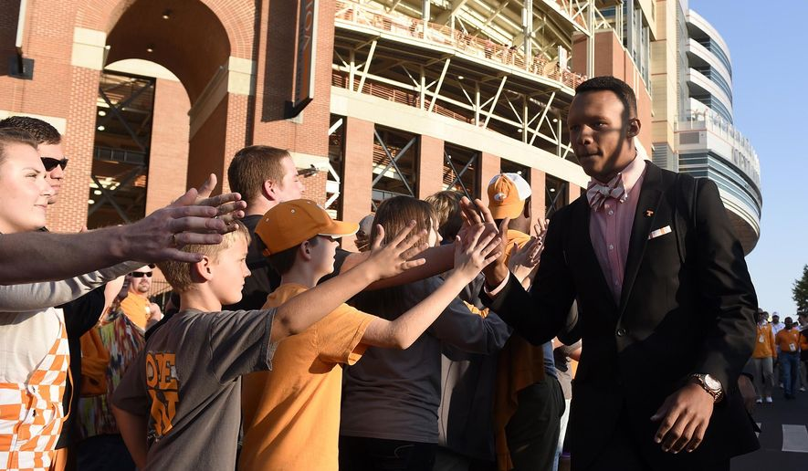 Tennessee quarterback Joshua Dobbs, right, makes his way through the Vol Walk before an NCAA college football game against Alabama at Neyland Stadium in Knoxville, Tenn., Saturday, Oct. 25, 2014. (AP Photo/The Knoxville News Sentinel, Kevin Martin)