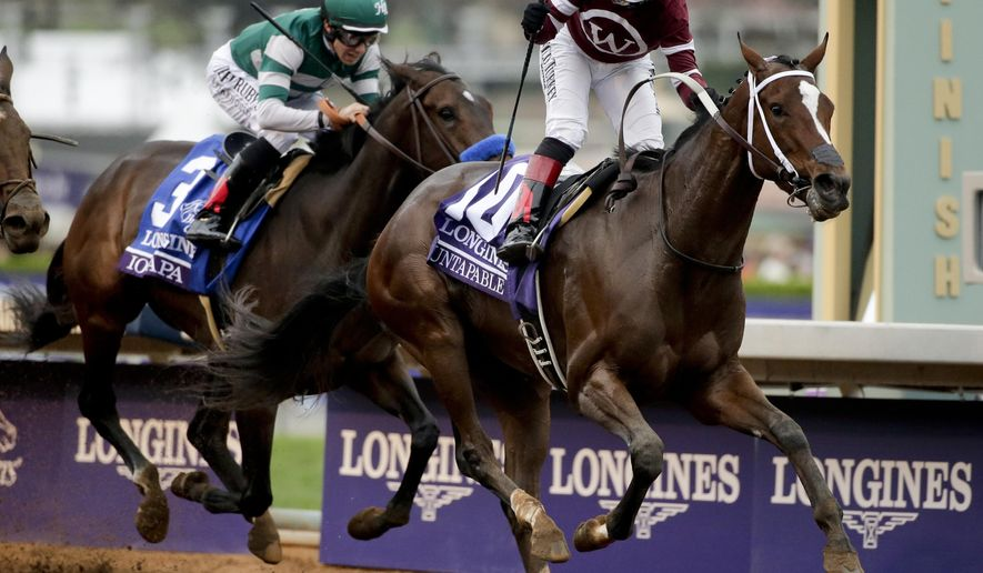 Rosie Napravnik, right, rides Untapable to victory ahead of Joseph Talamo on Iotapa in the Breeders' Cup Distaff horse race at Santa Anita on Friday, Oct. 31, 2014, in Arcadia, Calif. (AP Photo/Jae C. Hong)