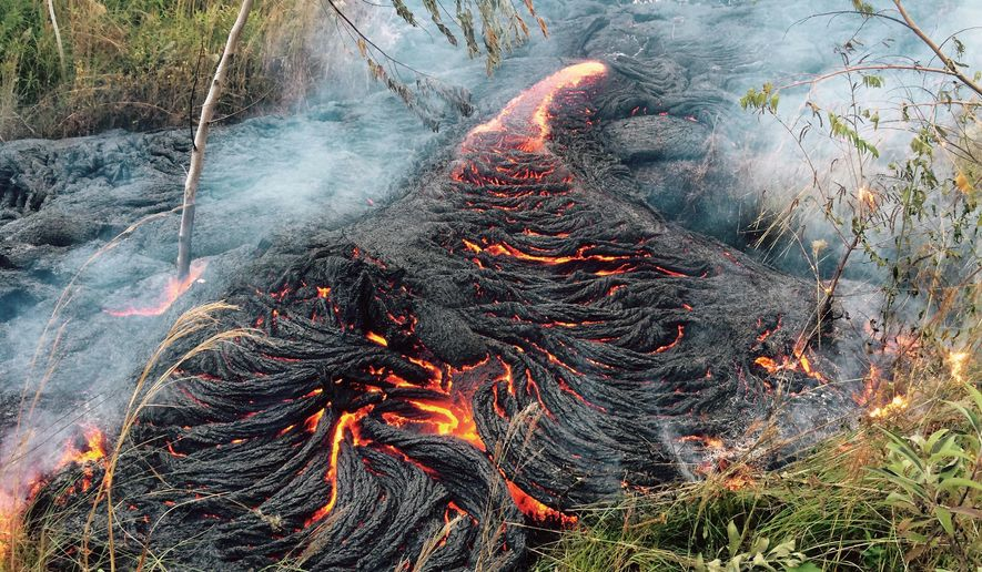 This Oct. 30, 2014 photo provided by the U.S. Geological Survey shows lava flow burning vegetation near the town of Pahoa on the Big Island of Hawaii. The Hawaii National Guard is deploying troops to a rural Hawaii town as lava makes a slow crawl toward a major road and threatens to further isolate the community that got its start during the lumber and sugar-plantation heyday. (AP Photo/U.S. Geological Survey)