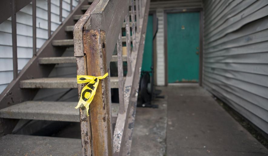 In this Tuesday, June 10, 2014 photo, residual crime scene tape remains tied to a staircase after authorities found a young girl dead at an apartment complex in southwest Houston. The Harris County Institute of Forensic Sciences said Thursday that Ayahna Comb died from malnutrition and dehydration and suffered from other ailments such as a bone infection and ruled the 9-year-old girl's death a homicide. (AP Photo/Houston Chronicle, Cody Duty)