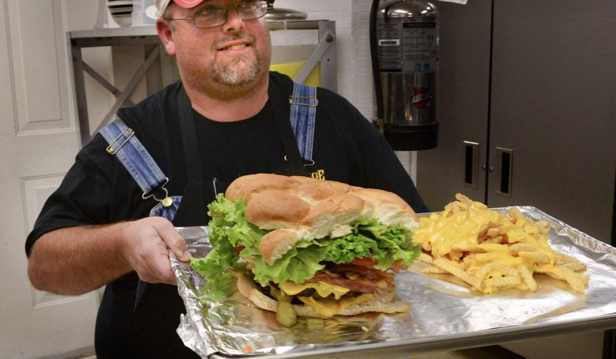 Marty Long carries out the Runaway Train Eating Challenge cheeseburger, with its accompanying 2 pounds of cheese fries, to challenger Jacob Whitaker at the Old Stage Grill in Yadkinville, N.C., Wednesday, Oct. 22, 2014.  Challengers put up $40 in advance. If they succeed in eating all the food in 45 minutes, they get their money back, a T-shirt and their name on the wall. If they lose, the restaurant keeps the $40. Whitaker didn't meet the challenge but was forgiven the $40 dollar fee.   (AP Photo/Winston-Salem Journal, David Rolfe)