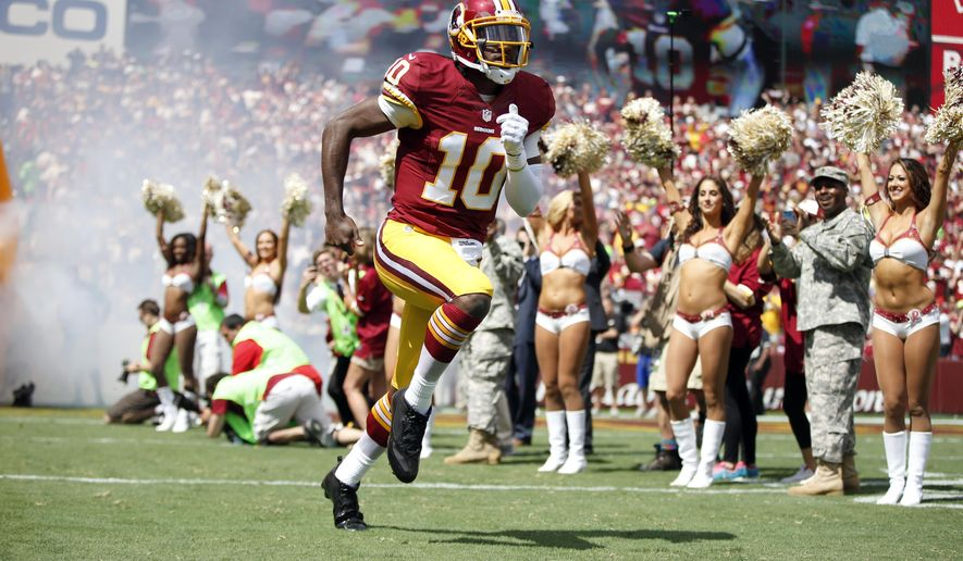 FILE - In this Sept. 14, 2014, file photo, Washington Redskins quarterback Robert Griffin III (10) runs on the field as he is introduced before an NFL football game against the Jacksonville Jaguars in Landover, Md. After six-plus games on the sideline, Robert Griffin III is back as the quarterback of the Washington Redskins for Sunday's, Nov. 2, 2014 game at Minnesota. (AP Photo/Evan Vucci, File)