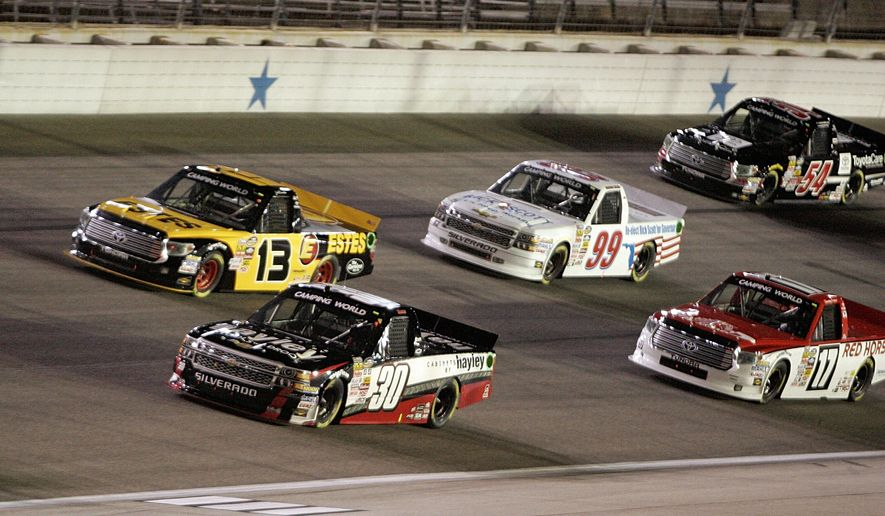 Drivers head through Turn 4 at the start of the NASCAR Trucks series auto race Friday, Oct. 31, 2014, in Fort Worth, Texas. (AP Photo/Fort Worth Star-Telegram, Bob Booth)