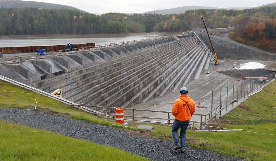 A worker walks near the 87-year-old Gilboa Dam in Gilboa, N.Y. on Thursday, Oct. 30, 2014. The structure underwent a $138 million reconstruction after inspections revealed the dam could potentially fail under extreme stress, raising alarms among the roughly 8,000 people living in the downstream towns and villages east of Albany. (AP Photo/Mike Groll)