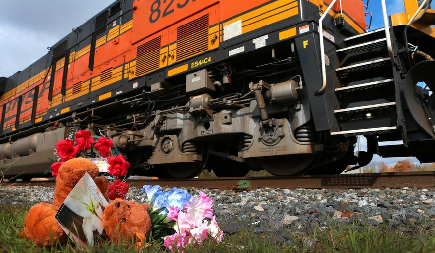 A tiny memorial sits beside the railroad tracks in downtown Vandalia on Friday, Oct. 31, 2014 where four members of a Greenville family were killed Thursday evening when a woman drove her SUV around safety gates.  A freight train struck the vehicle. (AP Photo/St. Louis Post-Dispatch, Robert Cohen)
