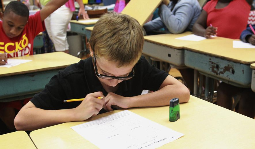 In this Aug. 18, 2014 photo, fifth-grade student Raymond Parks finishes a worksheet on core values on the first day of classes at Union Elementary School in Belleville, Ill. The yearly report card on Illinois schools released Friday, Oct. 31, 2014, contains a host of new features and benchmarks for measuring performance that Illinois Schools chief Christopher Koch says will give parents a more accurate picture in sizing up schools. (AP Photo/Belleville News-Democrat, Derik Holtmann)