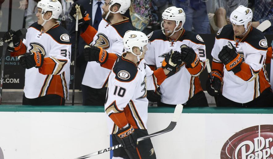 Anaheim Ducks right Wing Corey Perry (10) bumps fists with right wing Jakob Silferberg (33) of Sweden, as he celebrates his goal with teammates on the bench during the second period of an NHL hockey game against the Dallas Stars Friday, Oct. 31, 2014, in Dallas. (AP Photo/Sharon Ellman)