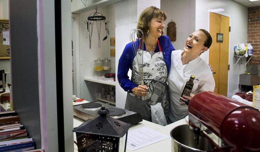 ADVANCE FOR USE SATURDAY, NOV. 1 AND THEREAFTER - In this Oct. 7, 2014 photo, Angela Anderson, left, and Katy Ferrell who have teamed up to open La Petite Cooking School, merging dining with a fun teaching environment that works in intimate sized classes share a laugh in Peoria, Ill.  Ferrell, 34, had another love along with cooking: dancing. A ballet dancer who danced professionally with a troupe that performed in places like Paris and Las Vegas, she also was part of a USO tour for troops based at the U.S. Naval Station at Guantanamo Bay in Cuba. With her dancing days over, Ferrell turned to the kitchen. (AP Photo/Journal Star, Fred Zwicky)