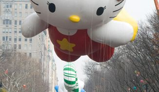 """FILE - In this Nov. 26, 2009 file photo, the Hello Kitty balloon floats down Central Park West during the Macy's Thanksgiving Day Parade in New York. When she came to life in 1974, she was a kitty without a name, sitting sideways in blue overalls and a big red bow, on a coin purse for Japanese girls. On Saturday, Nov. 1, 2014, fans around the world celebrate the 40th anniversary of this global icon of """"cute-cool."""" That is, Hello Kitty. (AP Photo/Charles Sykes, File)"""