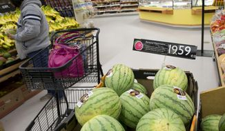 A shopper looks at bananas behind a display of small watermelons selling for $19.59 at the main general store in Barrow, Alaska, Wednesday, Oct. 8, 2014. (AP Photo/Gregory Bull) ** FILE **