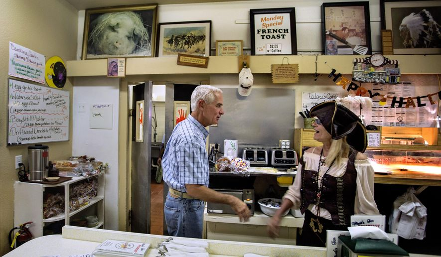 Democrat Charlie Crist  talks with server Carmen Taylor behind the counter at Munch's Restaurant & Sundries, Friday, Oct. 31, 2014 in St. Petersburg, Fla.  Crist is facing Gov. Rick Scott in the general election.  (AP Photo/The Tampa Bay Times, Cherie Diez) TAMPA OUT; CITRUS COUNTY OUT; PORT CHARLOTTE OUT; BROOKSVILLE HERNANDO TODAY OUT