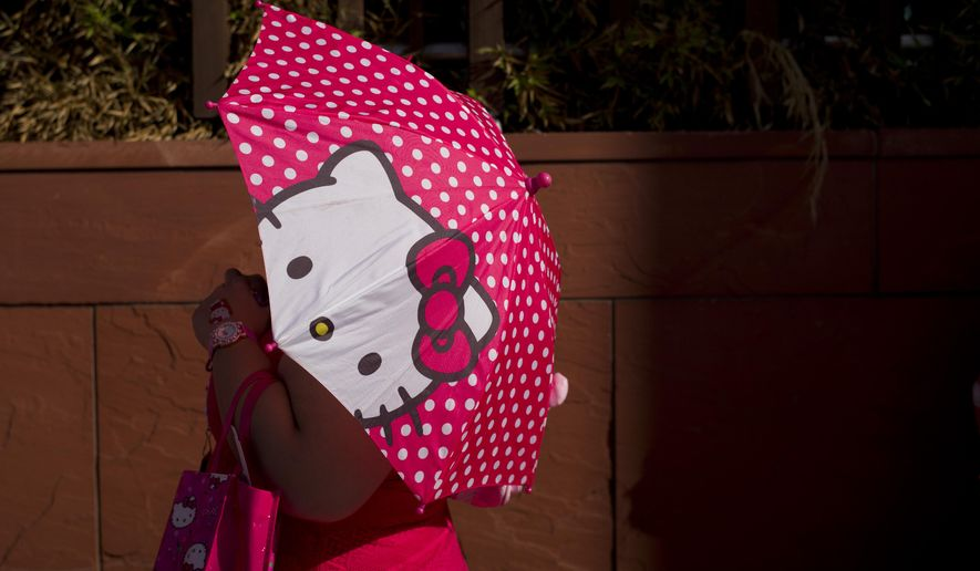A woman uses a Hello Kitty umbrella to shelter from the sun while waiting in line for the Hello Kitty Con, the first-ever Hello Kitty fan convention, held at the Geffen Contemporary at MOCA Thursday, Oct. 30, 2014, in Los Angeles. The convention was held to honor the character's 40th birthday. (AP Photo/Jae C. Hong)