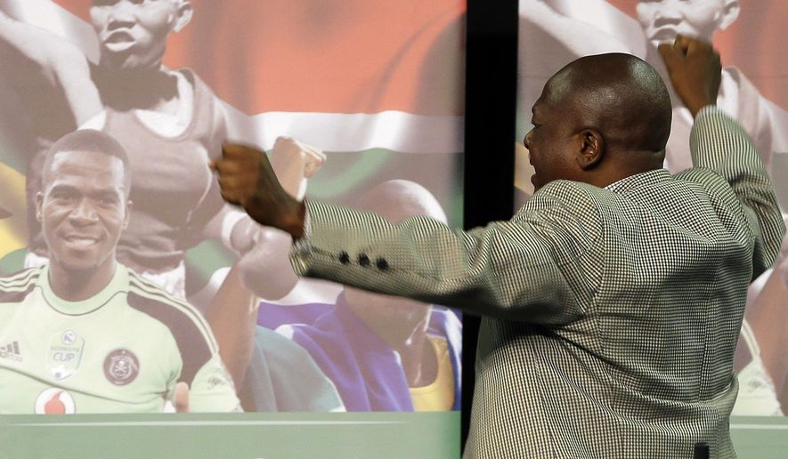 Sam Meyiwa, the father of national soccer captain and goalkeeper Senzo Meyiwa, bottom left, reacts as he walks past a poster with his son's portrait during a memorial service held for three South African sports figures who died within days of each other at an indoor sports arena in downtown Johannesburg, South Africa, Thursday, Oct. 30, 2014. South Africa's sport ministry organized a combined memorial service for fans of national soccer captain and goalkeeper Senzo Meyiwa, Olympic silver medalist Mbulaeni Mulaudzi and welterweight boxer Phindile Mwelase. (AP Photo/Themba Hadebe)