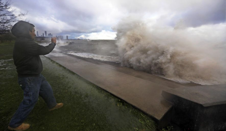 Manuel Hernandez takes video of high waves crashing into a break wall on the south shore of Lake Michigan, Friday, Oct. 31, 2014, in Chicago. Winds gusting up to 65 mph caused Lake Michigan waves to slam into the Chicago shoreline. The waves slowed traffic along Lake Shore Drive and prompted the cancellation of a Halloween attraction. (AP Photo/M. Spencer Green)
