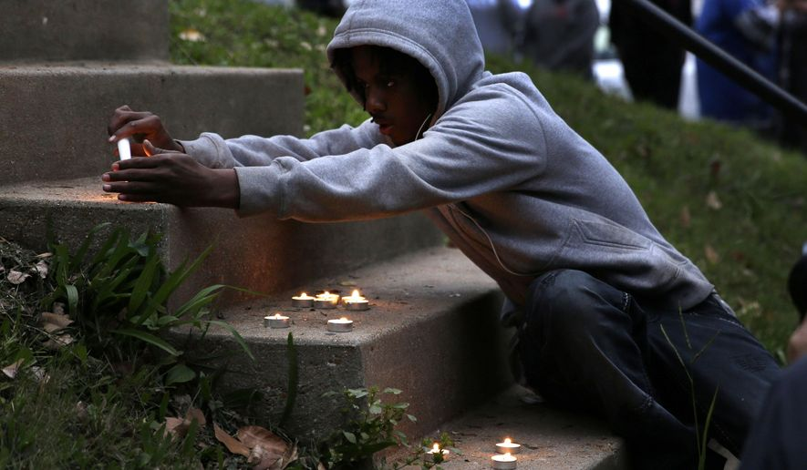 FILE - In this Thursday, Oct. 9, 2014 file photo, a boy lights candles during a vigil to remember VonDerrit Myers Jr., who was shot in October by an off-duty officer wearing his uniform and carrying his department-issued handgun, in St. Louis. A new unit that investigates police shootings will soon send its report on the 18-year-old's death to prosecutors, according to the St. Louis police chief. (AP Photo/Jeff Roberson, file)