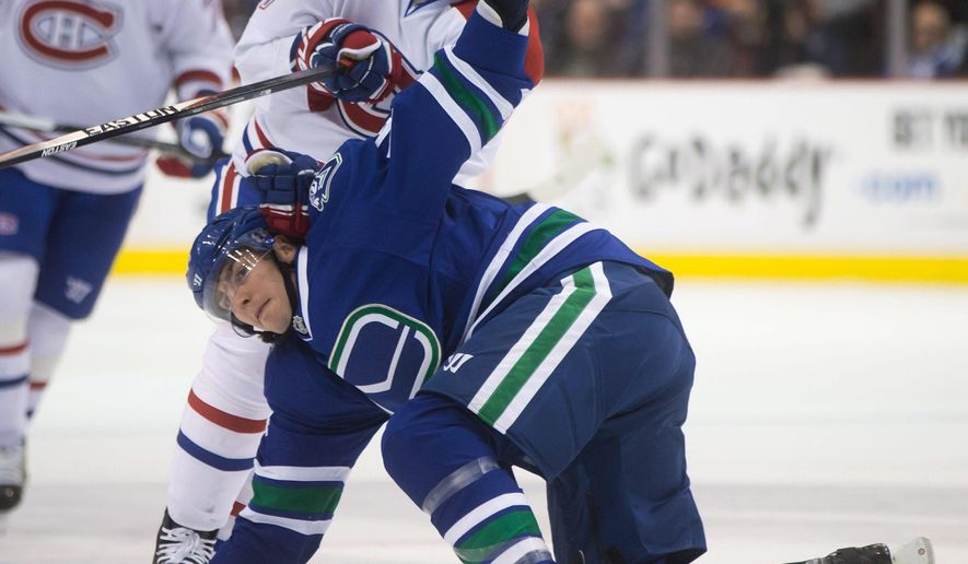 Montreal Canadiens 'Rene Bourque, back, checks Vancouver Canucks' Alex Burrows during the first period of an NHL hockey game, Thursday, Oct. 30, 2014 in Vancouver, British Columbia. (AP Photo/The Canadian Press,  Darryl Dyck)