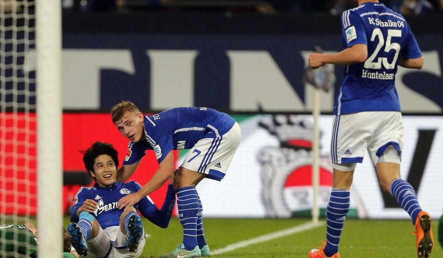Schalke's Klaas Jan Huntelaar from the Netherlands, right, Schalke's Max Meyer, center, and Schalke's Atsuto Uchida from Japan celebrate after scoring during the German first division Bundesliga soccer match between Schalke 04 and FC Augsburg in Gelsenkirchen, Germany, Friday,Oct. 31, 2014. (AP Photo/Frank Augstein)