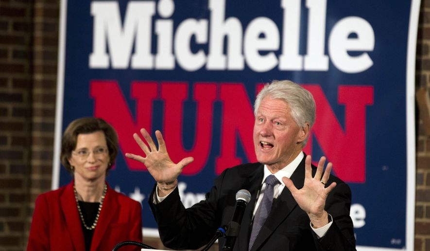 Former President Bill Clinton speaks as Democratic candidate for U.S. Senate Michelle Nunn looks on during a rally in Atlanta Friday, Oct. 31, 2014.  (AP Photo/John Bazemore)