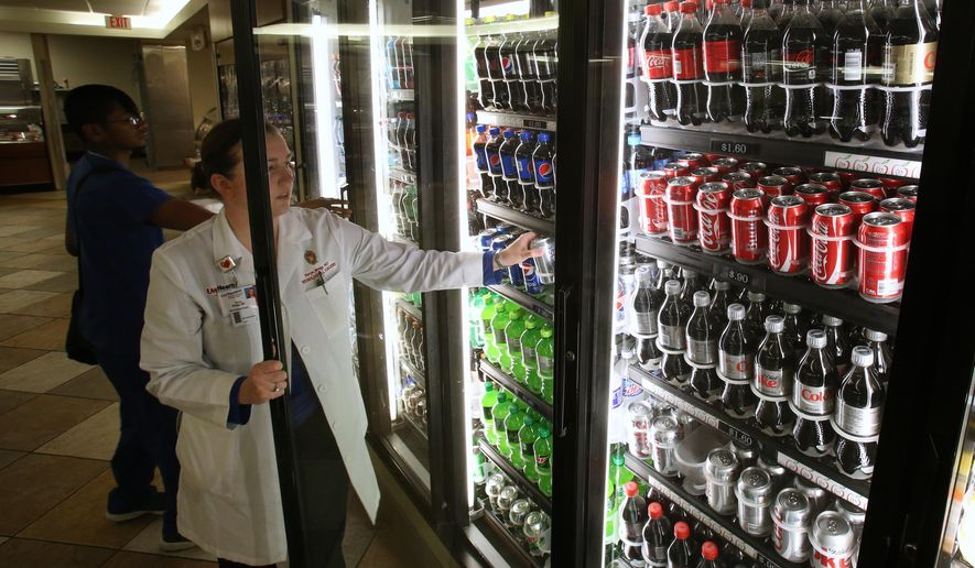 In this Aug. 26, 2014 photo, Dr. Taryn Bragg, pediatric neurosurgeon, grabs a beverage from the cooler at Four Lakes Cafe at UW Hospital in Madison, Wisc. UW Health says it will remove sugary drinks, as well as the deep fryers at UW Hospital, from its facilities by the end of the year. (AP Photo/Wisconsin State Journal, Amber Arnold)