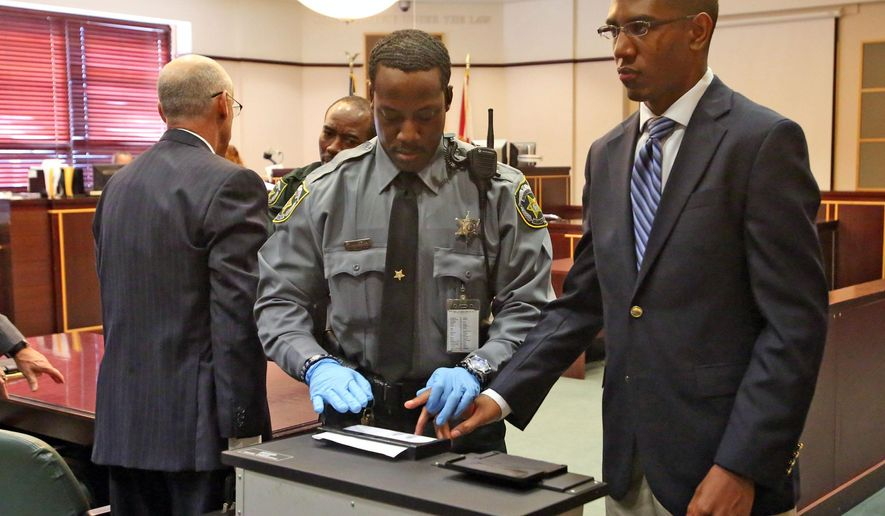 Dante Martin, right, a former member  of Florida A&M University's Marching 100 band looks at his family as he is fingerprinted  Friday, Oct. 31, 2014, after being  found guilty of manslaughter in the fatal hazing of drum major Robert Champion. Martin faces up to 22 years in prison, was found guilty of felony hazing and two misdemeanor counts of hazing involving two other band members. (AP Photo/Orlando Sentinel, Red Huber, Pool)