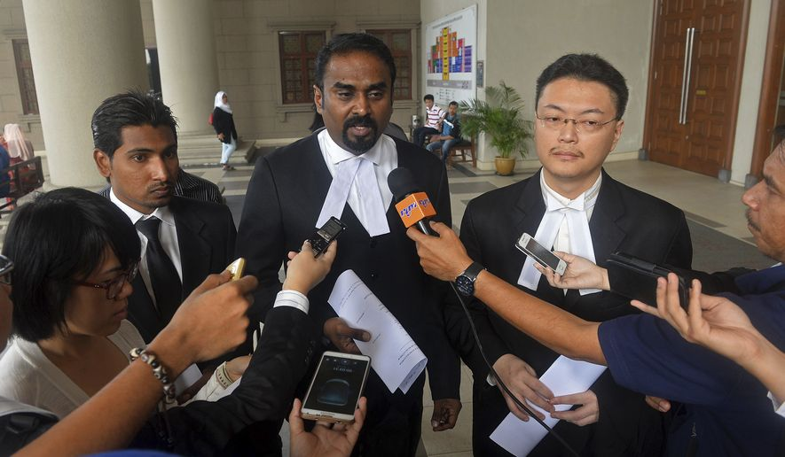 Malaysian lawyer Arunan Selvaraj, center, speaks to journalists outside a courthouse in Kuala Lumpur, Malaysia, Friday, Oct. 31, 2014. Two Malaysian teenage boys on Friday sued Malaysia Airlines and the government over the loss of their father on Flight 370, the first lawsuit filed by the family of a passenger of the jetliner that mysteriously disappeared eight months ago. (AP Photo) MALAYSIA OUT