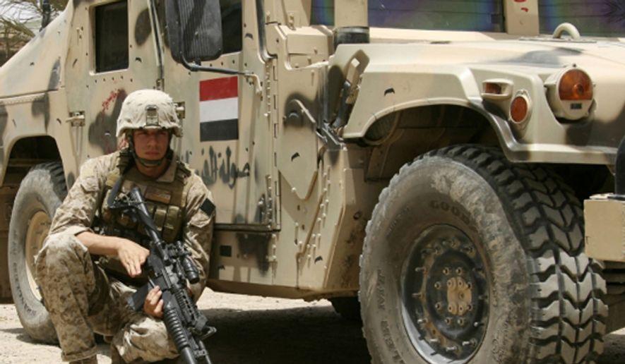 A U.S. Marine provides security in Baghdad. (Associated Press) ** FILE **