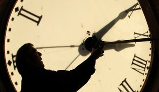 FILE - Custodian Ray Keen checks the time on a clock face after changing the time on the 97-year-old clock atop the Clay County Courthouse, in this Nov. 6, 2010 file photo taken in Clay Center, Kan. Most Americans will be able to get an extra hour of sleep Sunday Nov. 2, 2014 thanks to the annual shift back to standard time. Officially, the change occurs at 2 a.m. Sunday, but most people will set their clocks back before hitting the sack Saturday night. (AP Photo/Charlie Riedel, File)