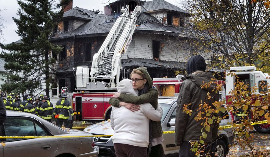Friends of a victim of a fatal apartment building fire console one another other Saturday, Nov. 1, 2014, in Portland, Maine. A fire swept through a two-apartment building housing students from the University of Southern Maine on Saturday morning, killing four people and critically injuring one, authorities said. They were still trying to account for several people who had been at a Halloween party at the building the night before. (AP Photo/Robert F. Bukaty)
