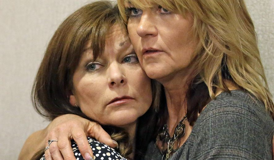FILE - In this Sept. 19, 2014, file photo, Susan Hunt, left, the mother of Darrien Hunt, is hugged by her sister, Cynthia Moss, during a news conference, in Salt Lake City. Authorities say a Saratoga Springs woman whose son was shot killed by police confronted officers during an unrelated traffic stop earlier this month. A spokesman for the city says Hunt pulled up behind two officers Oct. 19, walked up to them and started yelling at them. City spokesman Owen Jackson says Hunt struck one of the officers. (AP Photo/Rick Bowmer, File)