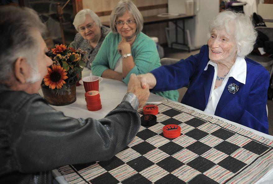 ADVANCE FOR SUNDAY NOV. 2 AND THEREAFTER - Phoebe Patton and Jim Austin shake hands after a competitive checkers game at Mount Carmel Baptist Church in Midland, Va. Phoebe Patton turned 100 years-old on Sept. 22, 2014. She is the checkers champion at church in Fauquier County. (AP Photo/The Free Lance-Star, Suzanne Carr Rossi)