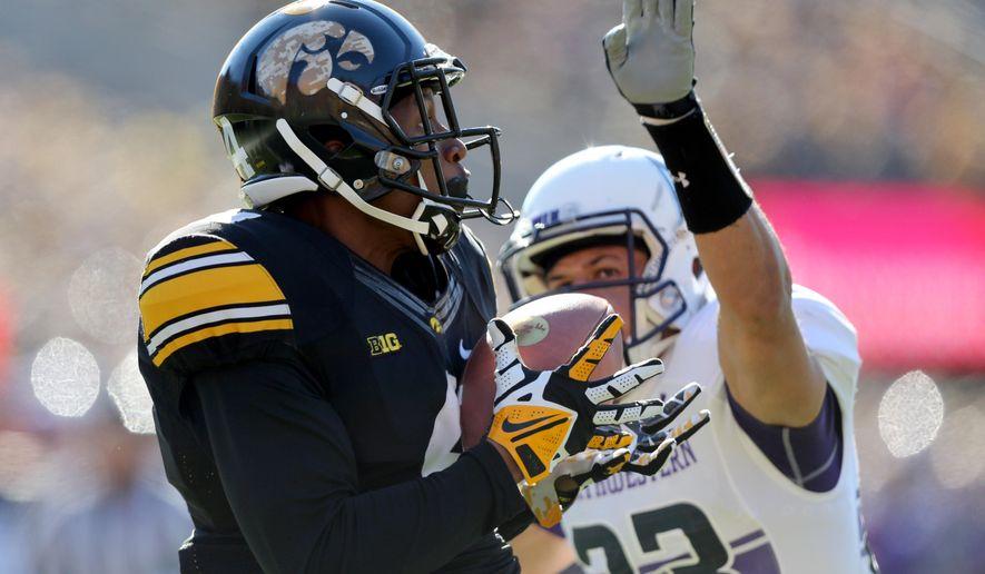 Iowa wide receiver Tevaun Smith (4) hauls in a touchdown pass over Northwestern cornerback Nick VanHoose (23) during the first half of an NCAA college football game, Saturday, Nov. 1, 2014, in Iowa City, Iowa . (Justin Hayworth/AP Photo)