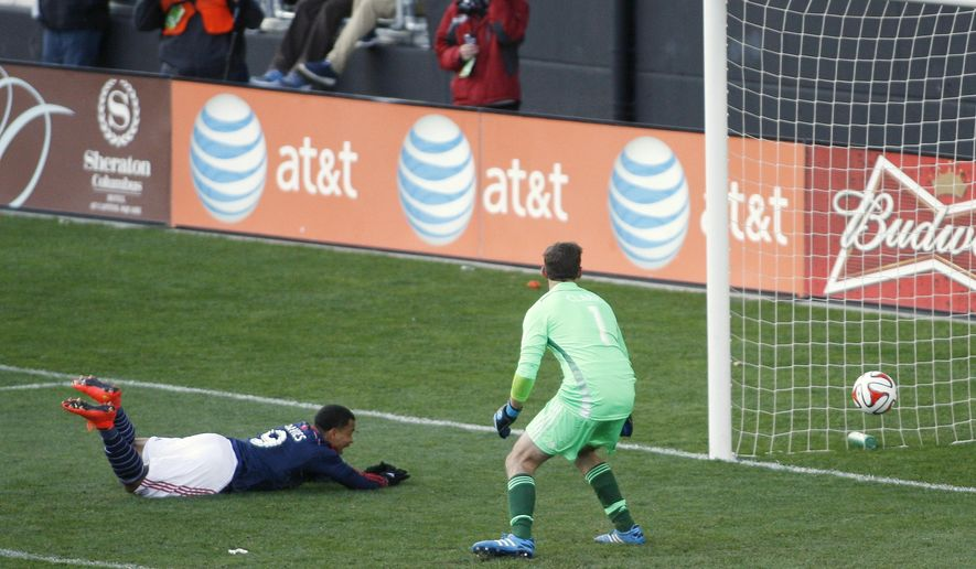New England Revolutions' Charlie Davies (9) scores against Columbus Crew goalie Steve Clark (1) on a set play during the first half of their MLS Cup playoff game, Saturday, Nov. 1, 2014, in Columbus, Ohio. (AP Photo/Mike Munden)