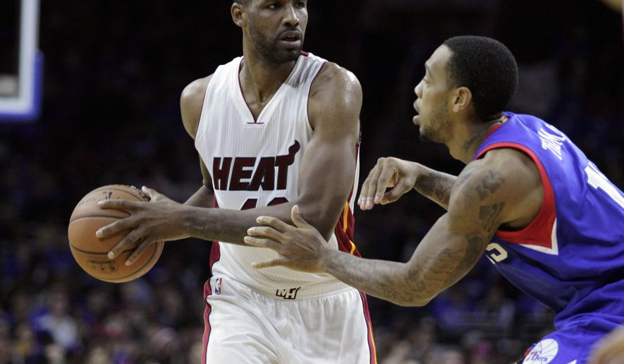 Miami Heat's Shawne Williams, left, looks to pass as Philadelphia 76ers' Malcolm Thomas defends in the first half of an NBA basketball game Saturday, Nov. 1, 2014, in Philadelphia. (AP Photo/ H. Rumph Jr)