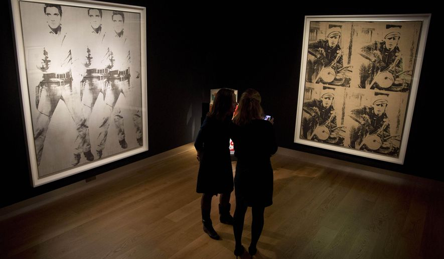 """FILE - In this Oct. 14, 2014, file photo, Christie's employees stand near U.S. artist Andy Warhol's """"Triple Elvis"""", left, a silkscreen ink and silver paint on linen and """"Four Marlons"""" a silkscreen ink on unprimed linen, on display at the offices of the auction house in London, . Potential bidders can expect to pay around $60 million for each when they feature in a post-war and contemporary art auction on November 12 in New York. (AP Photo/Matt Dunham, File)"""