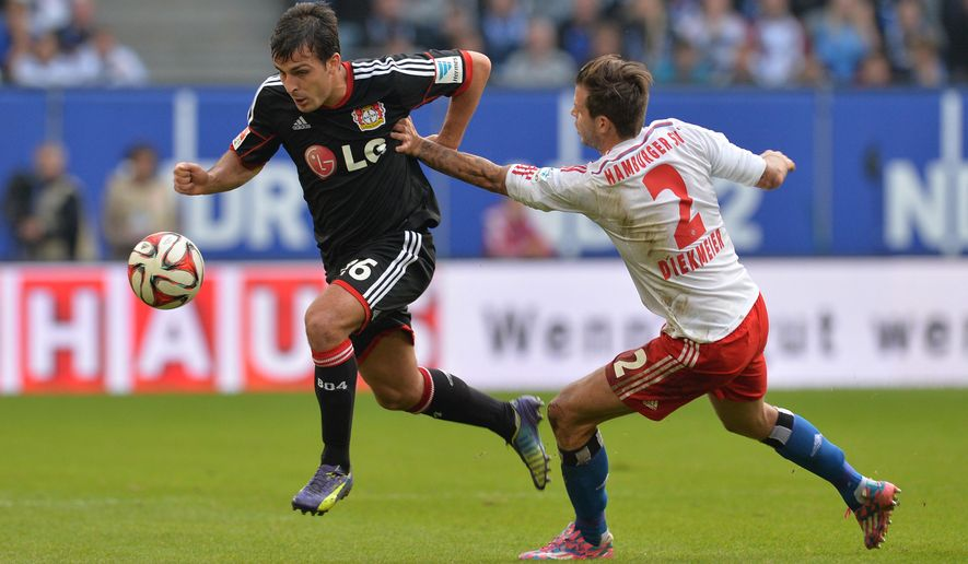 Hamburg's Dennis Diekmeier, right, and Leverkusen's Giulio Donati challenge for the ball during the German first division Bundesliga soccer match Hamburger SV and Bayer 04 Leverkusen at the Imtech Arena in Hamburg, Germany, Saturday, Nov. 1, 2014. (AP Photo/dpa, Carmen Jaspersen)