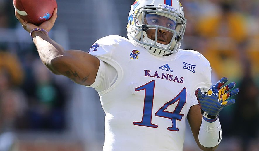 Kansas quarterback Michael Cummings (14) passes against Baylor  in the first half of an NCAA college football game, Saturday, Nov. 1, 2014, in Waco, Texas. (AP Photo/ Jerry Larson)
